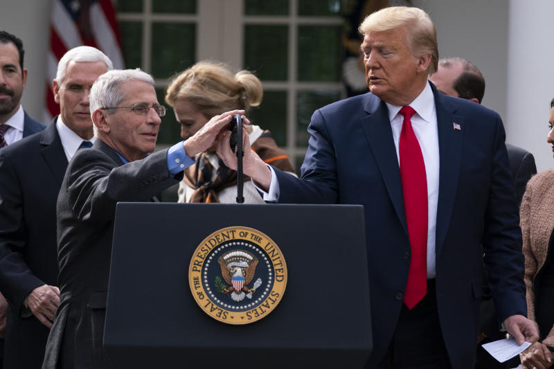 Dr. Anthony Fauci, director of the National Institute of Allergy and Infectious Diseases, adjusts the microphone to speak during a news conference on the coronavirus with President Donald Trump in the Rose Garden at the White House, Friday, March 13, 2020, in Washington. (AP Photo/Evan Vucci)
