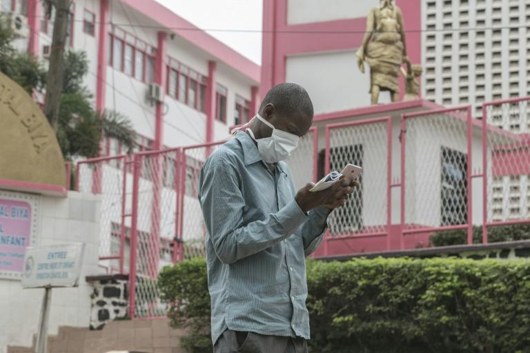 A man wears a mask while walking outside the entrance to the Yaounde General Hospital in Yaounde, Cameroon on March 6