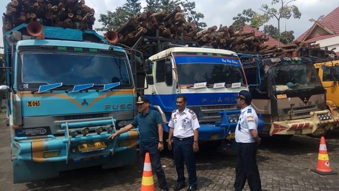 Petugas BPTD Riau-Kepri membawa empat truk ODOL ke Terminal AKAP Pekanbaru sebagai barang bukti. (Liputan6.com/M Syukur)