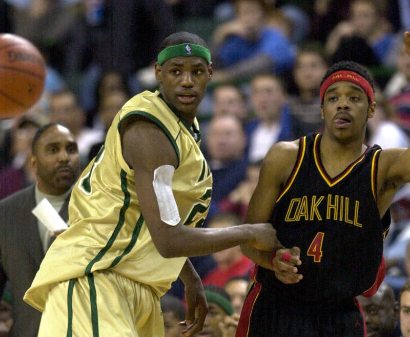 Akron St. Vincent-St. Mary's LeBron James, left, guards Isaiah Swann (4) of Virginia's Oak Hill Academy during the first half of a nationally televised high school game Thursday, Dec. 12, 2002, in Cleveland. James is perhaps the most talked about high school basketball player ever and the probable No. 1 overall pick in next year's NBA draft. (AP Photo/Mark Duncan)