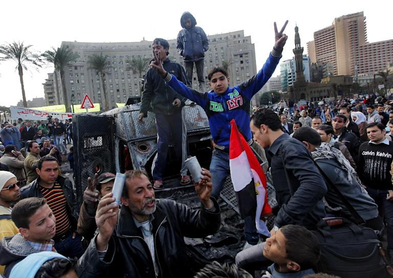 """Egyptian protesters celebrate the capture of a state security armored vehicle that demonstrators commandeered during clashes with security forces and brought to Tahrir Square in Cairo, Egypt, Tuesday, Jan. 29, 2013. Egypt's army chief warned Tuesday of the """"the collapse of the state"""" if the political crisis roiling the nation for nearly a week continues, but said the armed forces will respect the right of Egyptians to protest. (AP Photo/Amr Nabil)"""