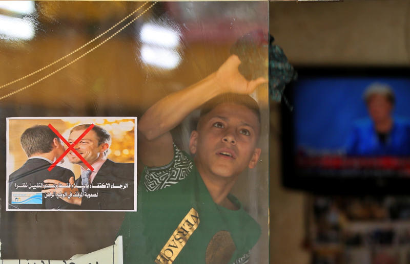 """File - In this Thursday, March 19, 2020 file photo, a young worker cleans the window of a barbershop that posts a warning sign referring to the coronavirus, with Arabic that reads, """"Please greet only and don't kiss, due to the difficult circumstances in the current situation,"""" in Baghdad, Iraq. Iraq announced a weeklong curfew to help fight the COVID-19 pandemic. (AP Photo/Hadi Mizban, File)"""