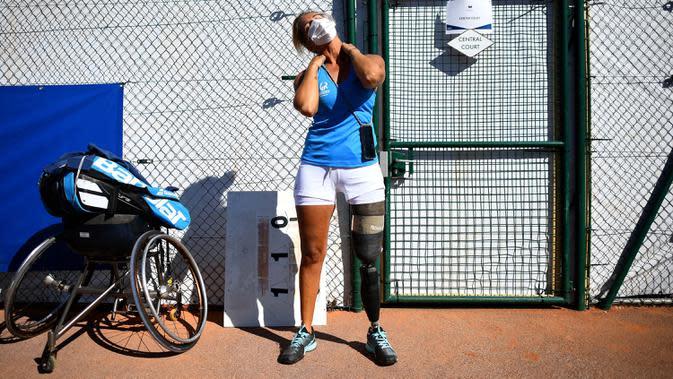 Atlet para tenis Prancis Pauline Deroulede melakukan strech sebelum pertandingan selama edisi ke-4 turnamen tenis kursi roda French Riviera Open di Biot, 28 September 2020. Pauline Deroulede saat ini tengah fokus terhadap Paralimpiade Paris 2024. (FRANCK FIFE/AFP)