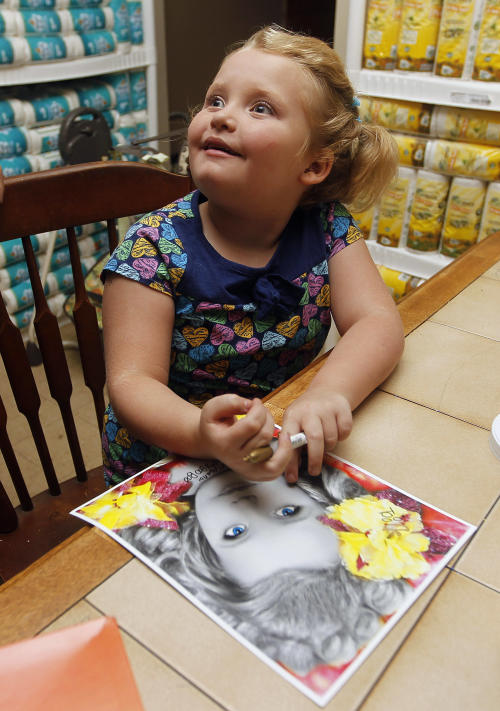 "In this photo taken Monday, Sept. 10, 2012, seven-year-old beauty pageant regular and reality show star Alana ""Honey Boo Boo"" Thompson signs a photo in her home in McIntyre, Ga. The reality show ""Here Comes Honey Boo Boo"" centers around Alana, her mother June Shannon and their family. (AP Photo/John Bazemore)"