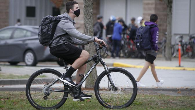 Seorang siswa yang mengenakan masker mengendarai sepeda ke sekolah di Vancouver, British Columbia, Kanada, 21 September 2020. Paparan COVID-19 telah dilaporkan di sedikitnya 20 sekolah di British Columbia sejak para siswa kembali belajar di sekolah dua pekan lalu. (Xinhua/Liang Sen)