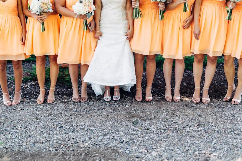 Low Section Of Bride With Bridesmaids Standing On Land