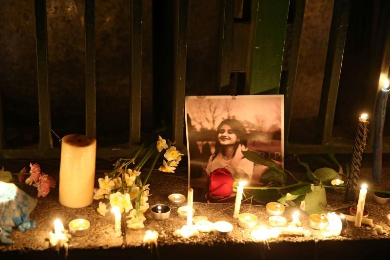 A picture is seen next to candles lit by people and families of the victims of the crash of the Boeing 737-800 plane, flight PS 752, in Tehran