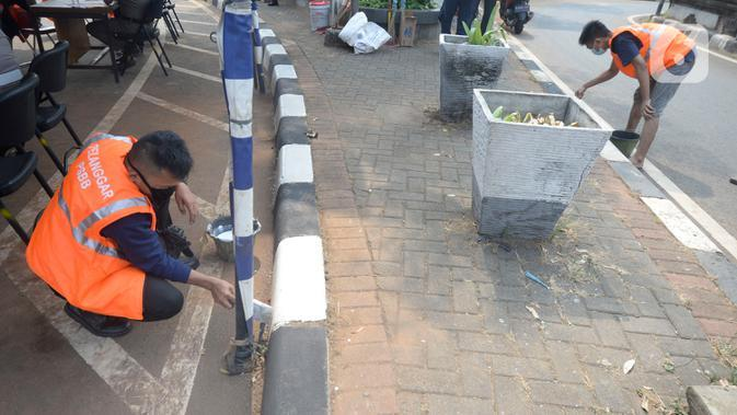Warga terkena sanksi sosial mengcat pembatas jalan kepada warga pelanggar karena tidak menggunakan masker di Lebak Bulus, Jakarta, senin (14/09/2020). Pemerintah Provinsi DKI Jakarta memperketat kembali PSBB karena kasus Covid-19 terus mengalami peningkatan. (merdeka.com/Dwi Narwoko)