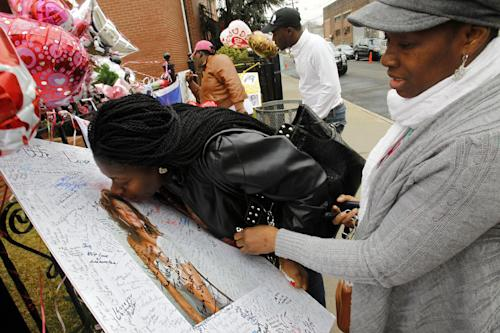 Yamda Johnson, kisses a signed photo of Whitney Houston as she and her friend Regina Kujemya both from Staten Island, N.Y., pay their respects at New Hope Baptist Church, in Newark, N.J., Wednesday, Feb. 15, 2012. The 48-year-old pop star was found dead in the bathtub in her hotel room at the Beverly Hilton Hotel on Saturday, hours before she was supposed to appear at a pre-Grammy gala. Houston's funeral will be held at the church on Saturday. (AP Photo/Rich Schultz)