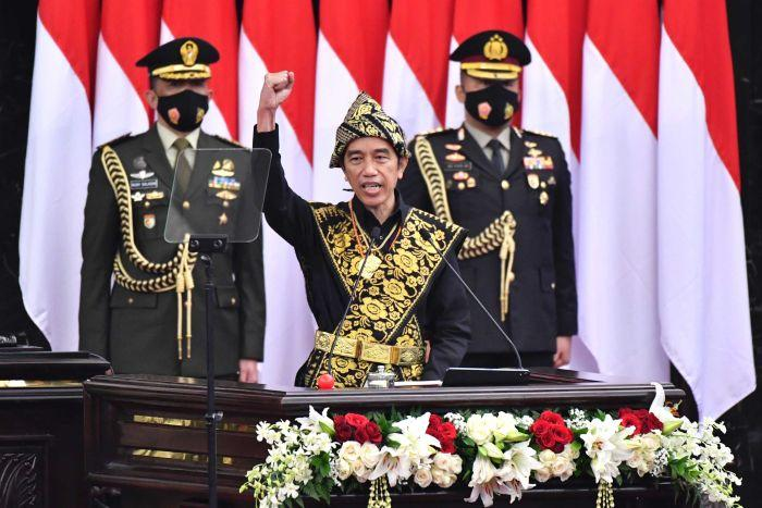 Indonesian President Joko Widodo, center, dressed in a traditional outfit, raises his fist as he delivers a speech.