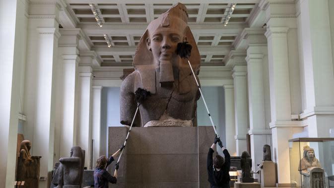 Sejumlah staf membersihkan debu pada permukaan sebuah benda pameran saat pratinjau media menjelang pembukaan kembali Museum Inggris di London, Inggris (25/8/2020). Museum tersebut akan dibuka kembali pada 27 Agustus. (Xinhua/Han Yan)