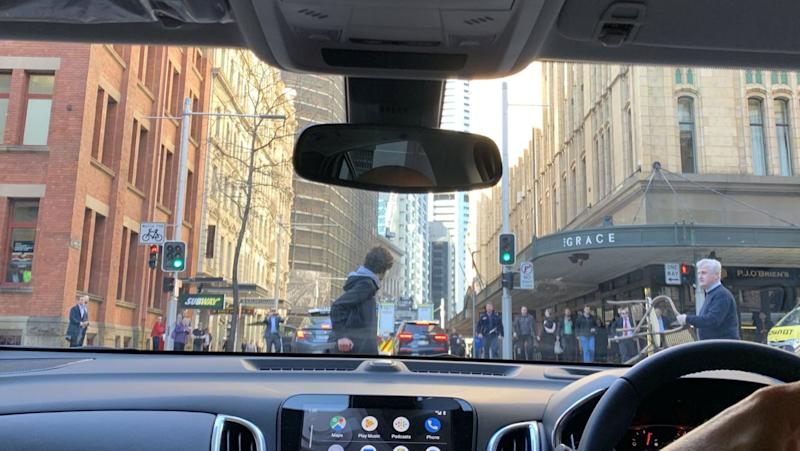 A photograph taken in Sydney's CBD from inside a car shows a man with a chair confronting the alleged stabber.