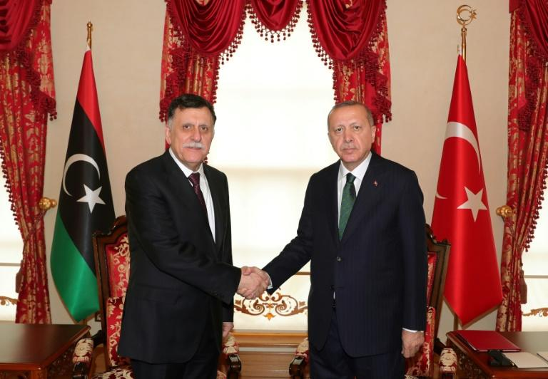 Turkey's President Recep Tayyip Erdogan (R) shakes hand with the head of Libya's Government of National Accord (GNA), Fayez al-Sarraj (L), at their meeting in Istanbul
