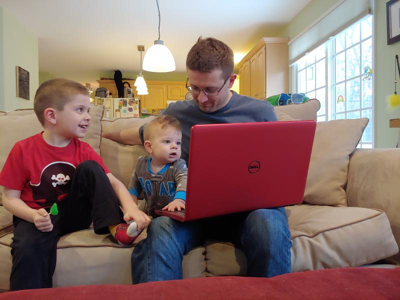 This image released by Caren Tolleth shows her husband Michael posing with their sons Gavin, 5, left, and Emmett, 9 months, at their home in Gillette, N.J. The coronavirus outbreak is having an impact on couples and their relationships. Some stay-at-home mothers say their husbands, now homebound, are finally having to see how much domestic work their spouses do.  (Caren Tolleth via AP)