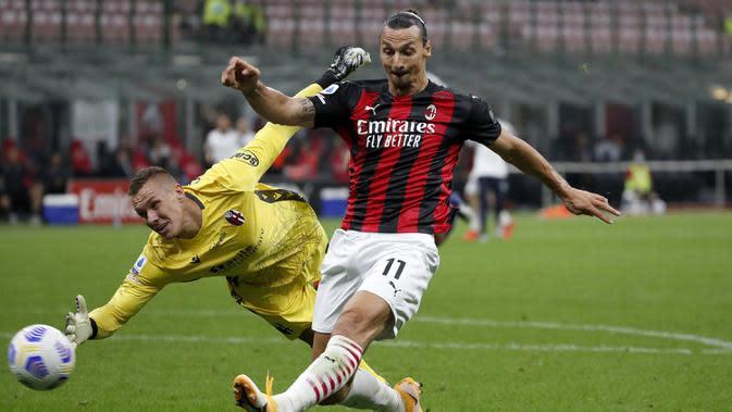 Pemain AC Milan Zlatan Ibrahimovic (kanan) menendang bola saat penjaga gawang Bologna Lukasz Skorupski mencoba menghentikannya pada pertandingan Serie A di Stadion San Siro, Milan, Italia, Senin (21/9/2020). AC Milan menaklukkan Bologna 2-0. (AP Photo/Antonio Calanni)