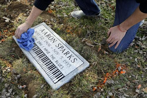 In this photo made Wednesday, Dec. 4, 2013, Aaron Pritchard wipes off a headstone after laying the marker on the previously unmarked grave of blues musician Aaron Sparks in Crestwood, Mo. Pritchard is part of the Killer Blues Headstone Project, a nonprofit effort to posthumously honor sometimes long-forgotten blues musicians with grave markers. The group has laid 22 headstones to date, with several more complete but awaiting placement. (AP Photo/Jeff Roberson)