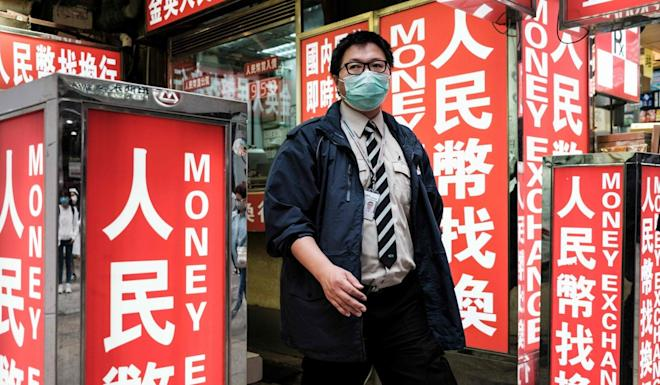 A security worker wears a face mask as he walks past a money exchange outlet in Hong Kong on March 1. Photo: Agence France-Presse