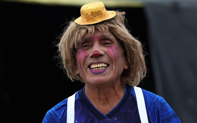 """Circus clown Santos Chiroque, whose performance name is """"Piojito"""", or Little Tick, laughs at his grandchild's comment that he looks like a woman, as he shows off his clown costume - AP Photo/Martin Mejia"""