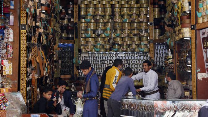 Warga membeli pisau belati tradisional di sebuah pasar menjelang Hari Raya Idul Fitri di Sanaa, Yaman, Jumat (22/5/2020). Idul Fitri menandai berakhirnya bulan suci Ramadan. (Xinhua/Mohammed Mohammed)