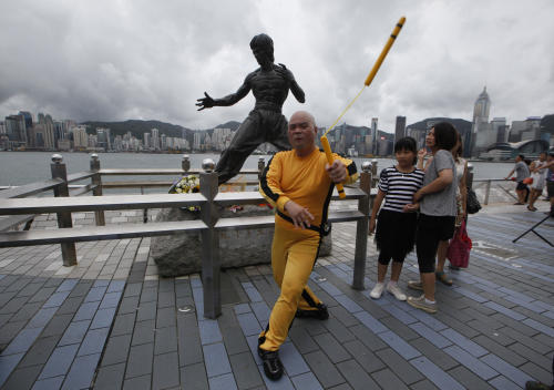 """A Japanese fan Kazuo Abe dressing as the late Hong Kong Kung Fu star Bruce Lee shows his skill of Nunchaku in front of the Lee's bronze statue in Hong Kong Saturday July 20, 2013 to commemorate the 40th anniversary of his death. The late superstar Bruce Lee is best-known for the kung fu skills he displayed in his movies, but his daughter hopes that more people take the effort to understand his teachings and life philosophy. Marking his death 40 years ago on July 20, the Hong Kong government has teamed up with the Bruce Lee Foundation to put together an exhibition to showcase the late star's life, from his famous yellow tracksuit he wore in the movie """"Game of Death,"""" to his writings and drawings. (AP Photo/Kin Cheung)"""