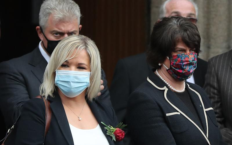 Northern Ireland Deputy First Minister Michelle O'Neill and First Minister Arlene Foster wearing face coverings during the funeral of John Hume at St Eugene's Cathedral in Londonderry - PA