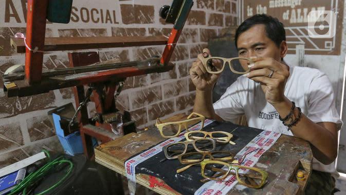 Pengrajin Yuyud, membuat kacamata dari limbah kayu di Jalan Salak, Pamulang, Tangerang Selatan, Senin (12/10/2020). Kacamata dari limbah kayu yang dijual dengan harga Rp 300 ribu hingga diatas Rp 1 juta mampu diproduksi 1-2 frame per hari. (Liputan6.com/Fery Pradolo)