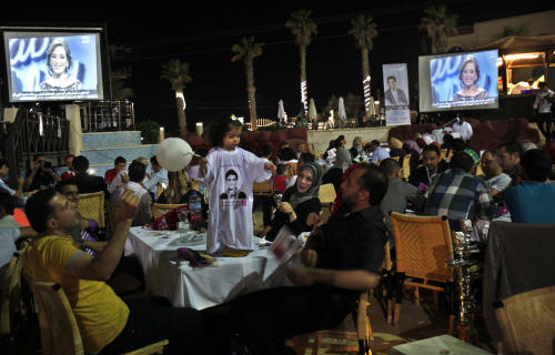 """Palestinians watch the televised performance of Mohamm3d Assaf, 23, a Palestinian finalist on the Arab Idol talent show, in Gaza City, Friday, June 21, 2013. Assaf, Gazan's powerful voice has propelled him to the final at the """"Arab Idol"""" in a TV talent contest choosing a winner in Beirut on Saturday. He is the first Palestinian to qualify for """"Arab Idol."""" (AP Photo/Adel Hana)"""