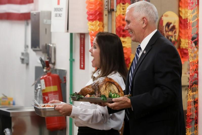 U.S. Vice President Pence and his wife help serve a Thanksgiving meal to U.S. troops in a dining facility at Camp Flores on Al Asad Air Base, Iraq
