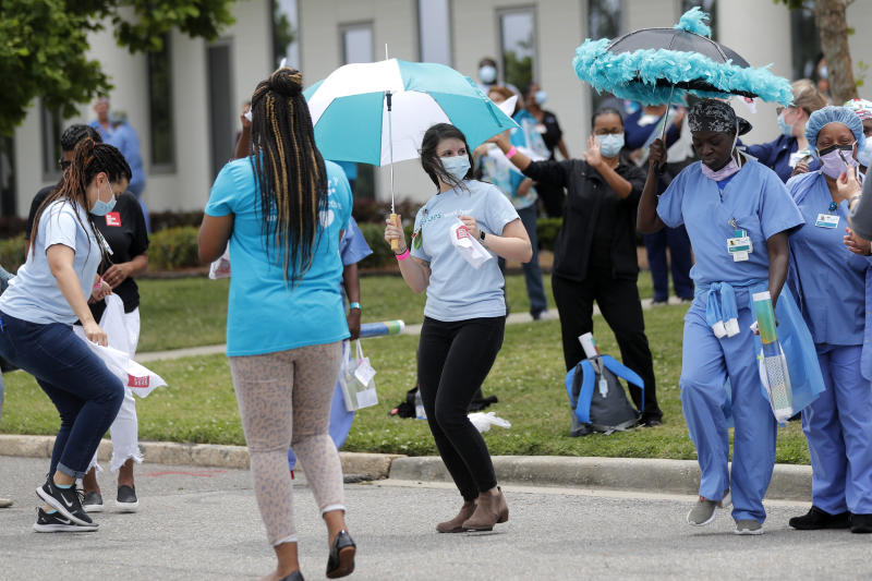 Healthcare workers at New Orleans East Hospital wave handkerchiefs and dance to a jazz serenade, as a tribute for their care of COVID-19 patients, by the New Orleans Jazz Orchestra, outside the hospital in New Orleans, Friday, May 15, 2020. A New York woman collaborated with the New Orleans Jazz Orchestra to put on what she calls a stimulus serenade to give moral support to front-line hospital workers and COVID-19 patients in New Orleans  (AP Photo/Gerald Herbert)