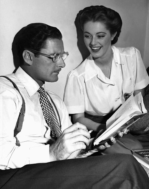 """FILE - In this Aug. 25, 1945 file photo, Errol Flynn seems to be in a literary mood as, between takes on the set of """"Never Say Goodbye,"""" he reads an amusing passage from a new novel to his leading lady, Eleanor Parker, who appears to enjoy the presentation in Los Angeles. Parker, a three-time Oscar nominee who played the scheming baroness in """"The Sound of Music,"""" has died at age 91. (AP Photo)"""