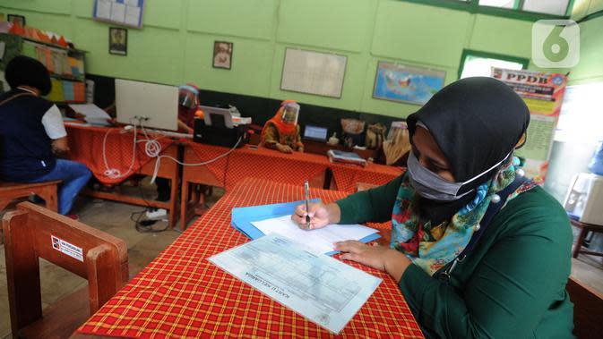 Orang tua siswa saat PPDB tahun ajaran 2020/2021di SDN Pengadilan I Bogor, Jawa Barat, Selasa (9/6/2020). Dinas Pendidikan Kota Bogor membuka waktu pendaftaran PPDB tingkat SD pada 8-11 Juni 2020. (merdeka.com/Arie Basuki)