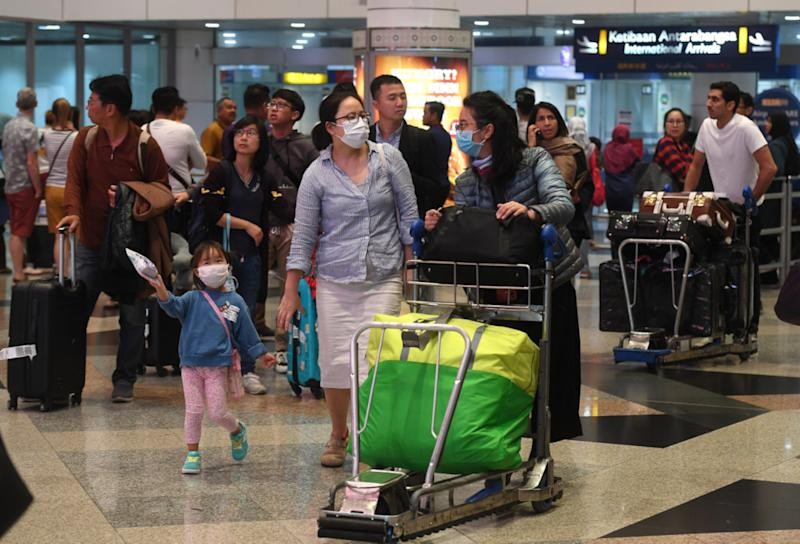 A family wears face masks at the arrival hall of the Kuala Lumpur International Airport January 24, 2020. — Bernama pic