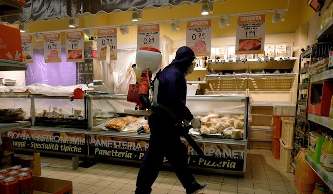 A man sanitises a supermarket in Rome, Italy, on Sunday. Photo: AP