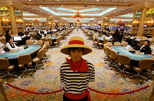 FILE - In this Aug. 28, 2007 file photo, gambling tables are set inside the casino during the opening ceremony of the Venetian Macao Resort Hotel in Macau. Attorneys began closing arguments Thursday, May 9, 2013, in the dispute between Las Vegas Sands and a fixer who says he helped the casino giant win a license in the Chinese gambling enclave of Macau. (AP Photo/Kin Cheung, File)