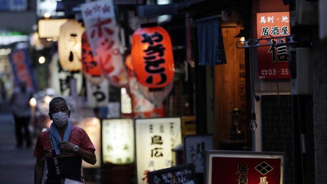 Seorang pria yang memakai masker untuk membantu mencegah penyebaran virus corona berjalan di sebuah jalan bar di Tokyo, Kamis (10/9/2020). Ibukota Jepang mengonfirmasi lebih dari 270 kasus virus korona pada hari Kamis. (AP Photo / Eugene Hoshiko)