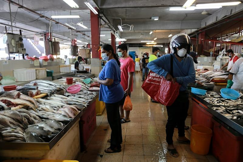 People buying fresh fish at a wet market in Petaling Jaya March 25,2020. — Picture by Ahmad Zamzahuri