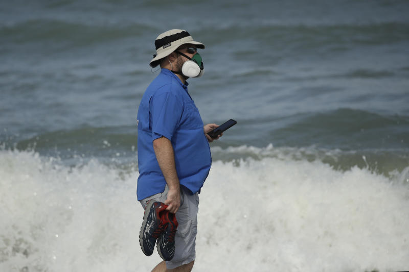 A man wears a mask to help prevent the spread of the coronavirus as he walks alone on the beach Sunday, May 31, 2020, at Satellite Beach, Fla. (AP Photo/Charlie Riedel)