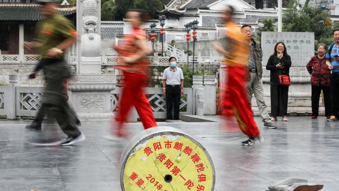 Anggota Klub Gasing Kylin Guiyang melakukan pemanasan sebelum memainkan sebuah gasing raksasa di Lapangan Jiaxiulou di Guiyang, Provinsi Guizhou, China barat daya, (15/5/2020). (Xinhua/Ou Dongqu)