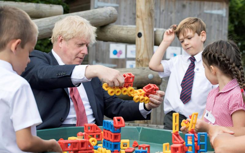 Britain's Prime Minister Boris Johnson plays with toys as students look on during a visit to The Discovery School in Kent, Britain July 20, 2020 - Jeremy Selwyn/Pool/Reuters