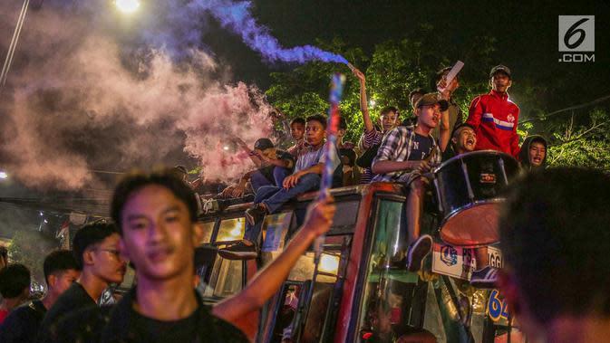 Warga konvoi menggunakan bus saat merayakan malam takbiran menyambut Hari Raya Idul Fitri 2019 di kawasan Tanah Abang, Jakarta, Selasa (4/6/2019). Pemerintah menetapkan Hari Raya Idul Fitri 1440 Hijriah jatuh pada hari Rabu 5 Juni 2019. (Liputan6.com/Faizal Fanani)