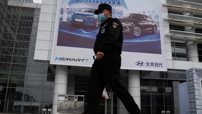 Seorang petugas keamanan berjalan melewati iklan untuk pameran Auto China 2020 yang akan digelar di Beijing, Kamis (24/9/2020). Menandai bangkitnya kembali industri otomotif negara dengan penduduk terbanyak di dunia ini, China mengumumkan siap menggelar Auto China 2020. (AP Photo/Ng Han Guan)