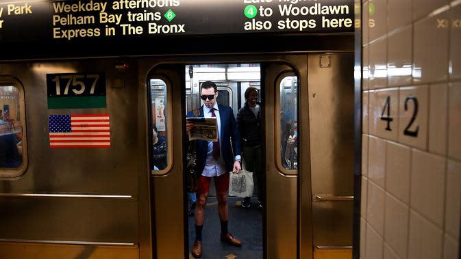 Peserta acara tahunan No Pants Subway Ride melakukan perjalanan dengan kereta bawah tanah di New York pada Minggu (12/1/2020). Untuk tahun ini, acara naik kereta tanpa celana itu dilangsungkan serentak di sejumlah kota dunia pada 12 Januari. (Johannes EISELE / AFP)