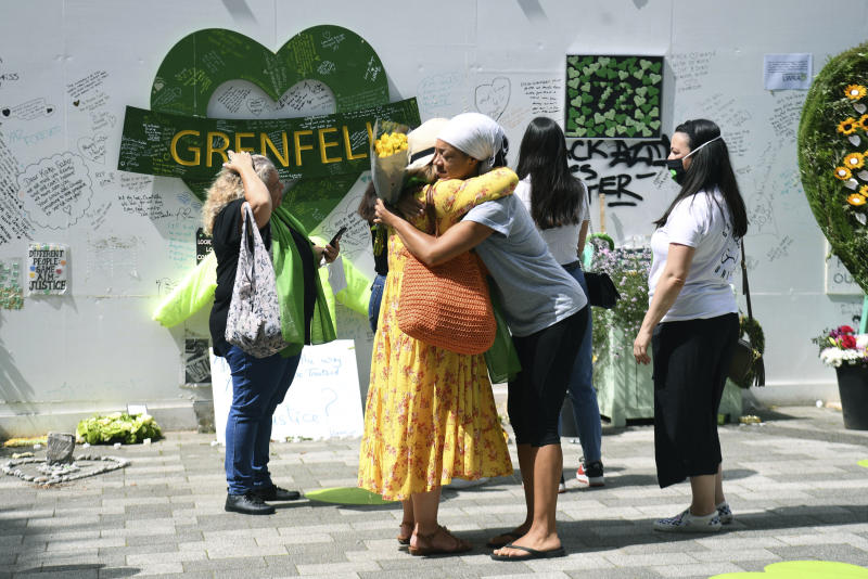 People hug in front of the Grenfell Memorial Community Mosaic at the base of the tower block in London, Sunday, June 14, 2020.  Britain is marking the third anniversary of the Grenfell Tower fire with a virtual church service to remember the 72 people who died in the blaze. Sunday marks three years since a small kitchen fire in the west London public-housing block turned into the worst domestic blaze in the country since World War II. (Kirsty O'Connor//PA via AP)