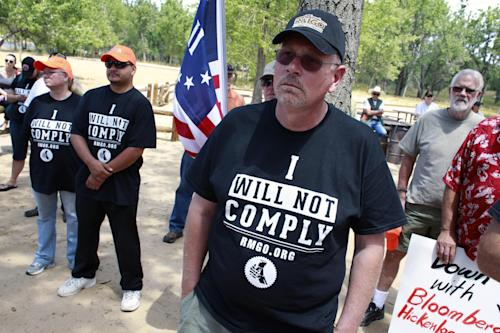 Participants listen to a speaker during a gun rights rally, held near a pro-gun control Mayors Against Illegal Guns remembrance event honoring the victims of the Aurora theater shootings, Friday, July 19, 2013, at Cherry Creek State Park in Aurora, Colo. Saturday, July 20 marks one year since the Aurora movie theater shooting rampage, which left 12 dead and 70 wounded. (AP Photo/Brennan Linsley)
