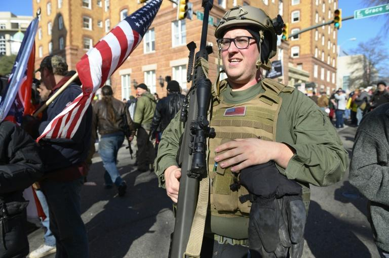 A pro-gun supporter from Buffalo, New York, carries a high-caliber sniper rifle during a gun rights rally by thousands of people outside the Virginia State Capitol grounds in Richmond, Virginia