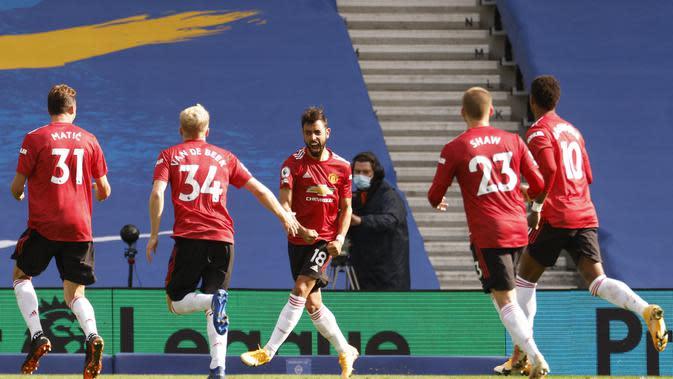 Sejumlah pemain Manchester United berlari ke arah Bruno Fernades usai sukses membobol gawang Brighton and Hove Albion lewat titik penalti, Sabtu (26/9/2020). (John Sibley/Pool via AP)