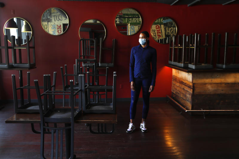 In this Thursday, May 21, 2020, image, Stephanie Byrd, co-owner of The Block, poses for a photo with chairs on the tables while the restaurant is closed due to the coronavirus in Detroit. She's worried other black-owned businesses will struggle to withstand another wave of economic uncertainty during the pandemic, following decades of inequity that made it hard for many to flourish in the first place. (AP Photo/Paul Sancya)