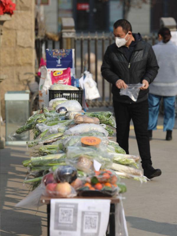 Seorang pria membeli sayuran di kios sayur tak berpenjaga di permukiman di Shijiazhuang, Provinsi Hebei, China utara (12/2/2020). Kios sayur tak berpenjaga itu didirikan untuk menyediakan sayuran kepada warga dengan kontak minimal sebagai upaya melawan epidemi virus corona. (Xinhua/Liang Zidong)