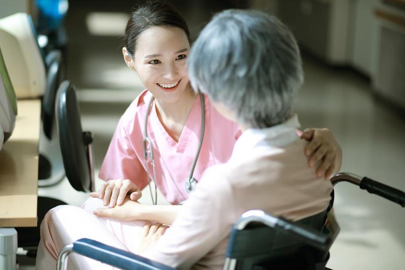 Nurse talking to senior woman in wheelchair