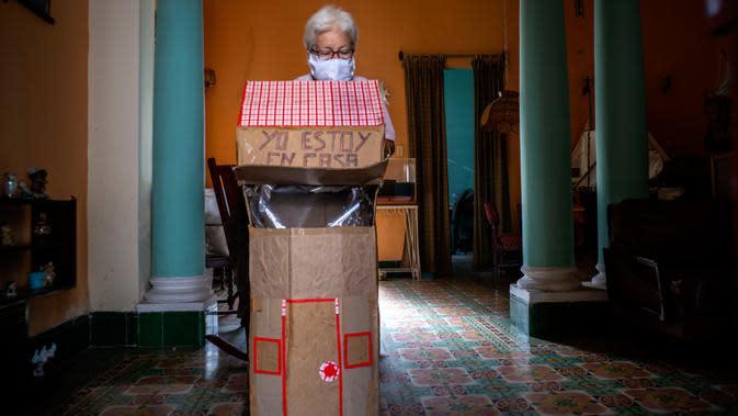 Pensiunan perawat, Feridia Rojas (82) bersiap mengenakan kotak kardus berbentuk rumah untuk melindungi dirinya dari penyebaran Covid-19 di Havana, Kuba, 8 Juli 2020. Pakaian pelindung kardus itu dipakai Rojas untuk melakukan aktivitas di luar rumah sehari-hari seperti berbelanja. (AP/Ramon Espinosa)